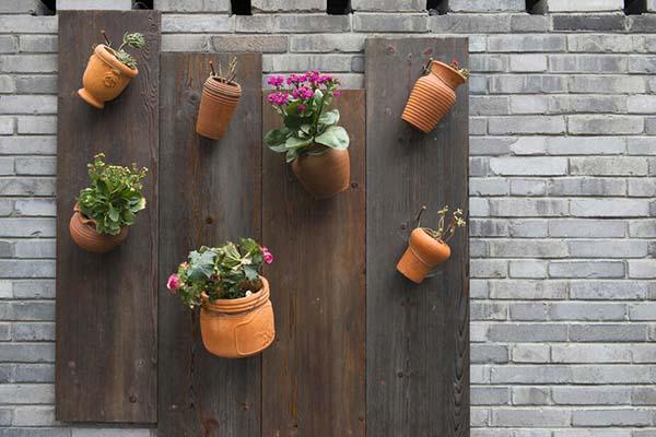 آویزان کردن گلدان روی پنل چوبی در بالکن